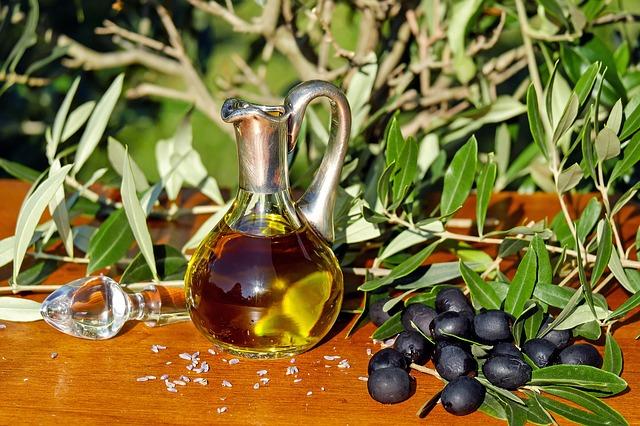 Olivový olej v sklenenej fľaši a čierne olivy.jpg