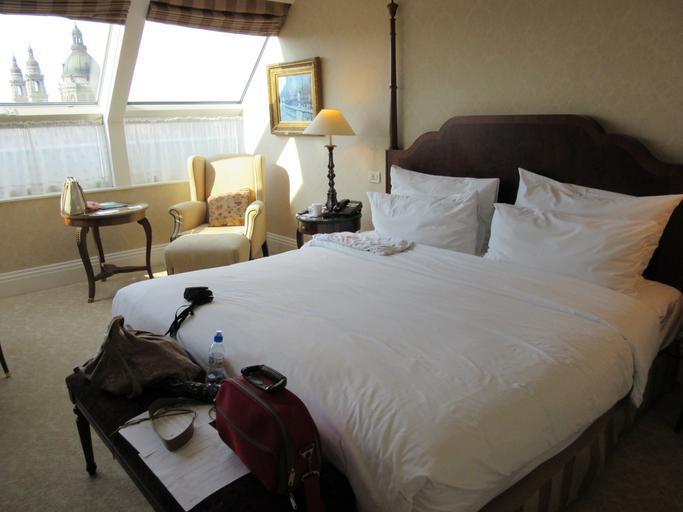 Veľká manželská posteľ v spálni s veľkými oknami.jpg