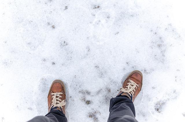 Muž v hnedých teniskách stojí v snehu.jpg